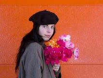 Boina vestindo e revestimento da menina moreno que guardam o ramalhete colorido foto de stock