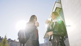 Boire de deux jeunes filles du jus frais froid tout en marchant dehors le jour chaud ensoleillé Les meilleures amies, mode de vie clips vidéos