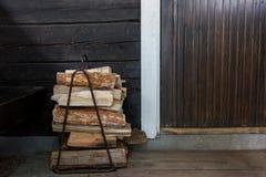 Bois de chauffage à côté de la porte ouverte au sauna finlandais traditionnel Images stock