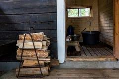 Bois de chauffage à côté de la porte ouverte au sauna finlandais traditionnel Image libre de droits