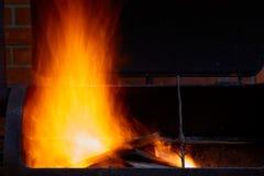 Bois de chauffage brûlant dans le barbecue à la fin d'arrière-cour  Photographie stock libre de droits