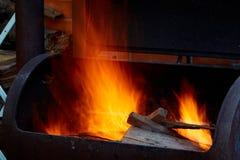 Bois de chauffage brûlant dans le barbecue à la fin d'arrière-cour  Photographie stock