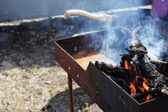 Bois de chauffage brûlant dans le vieux gril de gril, faisant cuire des chiches-kebabs photographie stock libre de droits