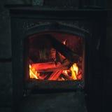 Bois de chauffage brûlant dans le petit fourneau noir de fer photographie stock
