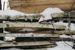 bois de chauffage couvert de neige empilé sous un auvent, bois de chauffage pour l'hiver Horizontal de l'hiver photo stock