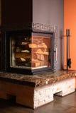 Bois de chauffage empilé dans le burning de début de cheminée Photos stock