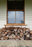 Bois de chauffage empilé sous la fenêtre Photographie stock