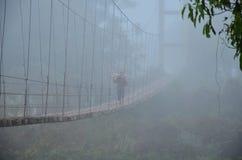 Bois de chauffage de transport de personnes thaïlandaises marchant sur le pont en bois de suspension Images stock