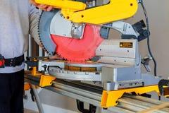 bois de coupe d'homme sur la scie électrique Images stock