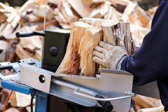 Bois de coupe de scie pour l'hiver Un bois de chauffage de coupe d'homme pour l'hiver utilisant un bois de charpente moderne de m photos stock