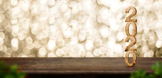 Bois de la bonne année 2020 avec l'étoile de scintillement sur la table en bois brune avec le fond de bokeh d'or, concept de fête photographie stock libre de droits