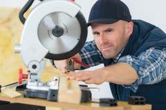 Bois de mesure de charpentier à couper avec la scie circulaire photos stock