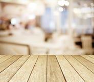 Bois de perspective au-dessus de restaurant brouillé avec le fond de bokeh, Photo stock