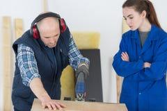Bois de rabotage de With Female Apprentice de charpentier dans l'atelier image stock