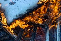 Bois, flamme et fumée brûlants sur le fond bleu Photographie stock libre de droits