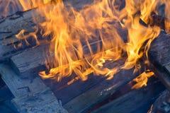 Bois, flamme et fumée brûlants sur le fond bleu Image libre de droits