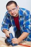 Bois travaillant d'homme avec une planeuse électrique Photographie stock libre de droits