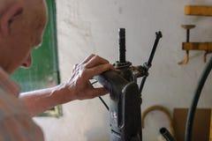 Bois travaillant d'homme de charpentier ou de constructeur avec la perceuse électrique image stock