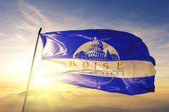 Boise-City Hauptstadt von Idaho des Flaggentextilstoffgewebes Vereinigter Staaten, das auf den Spitzensonnenaufgangnebelnebel wel stockbilder