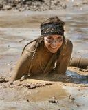 BOISE, IDAHO/USA - 25-ое августа - неопознанная женщина сидит в пруде грязи с огромной улыбкой во время пакостной черточки. Пакост Стоковая Фотография