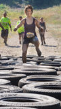 BOISE, IDAHO/USA - AUGUST 10: Runner 10951 does high knees to get past the tire obstacle at the The Dirty Dash in Boise, Idaho on Royalty Free Stock Photos