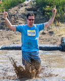 BOISE, IDAHO/USA - AUGUST 10: Runner 40518 makes a small splash while throwing up the devil horns at the The Dirty Dash in Boise, Stock Image