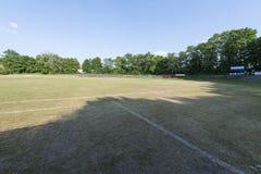 Boisko do piłki nożnej z celami, drzewami i niebieskim niebem, fotografia royalty free