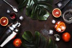 Boisson à la mode, cocktail alcoolique Negroni avec le genièvre sec, vermouth rouge et tranche rouge et glaçons amers et oranges  images libres de droits