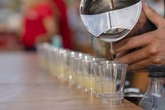 Boisson alcoolisée de versement dans des verres à liqueur dans une rangée photo stock