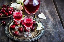 Boisson alcoolisée faite maison de cerise en verres d'un vintage sur le plateau et les cerises en métal Photo stock