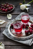 Boisson alcoolisée faite maison de cerise en verres d'un vintage sur le plateau et les cerises en métal Photographie stock libre de droits