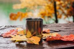 Boisson chaude dans la tasse en acier sur la table en bois Autumn Orange Leaves images stock