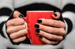 Boisson chaude dans une tasse rouge dans des ses mains Photographie stock