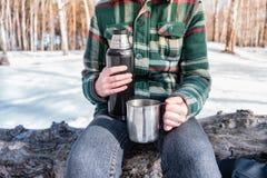 Boisson chaude de versement hors de thermos à un terrain de camping photos stock