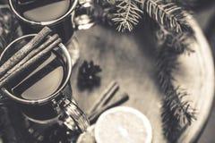 Boisson chaude de vin chaud avec l'agrume et les épices dans une tasse en verre et la branche impeccable sur un fond concret Photographie stock libre de droits