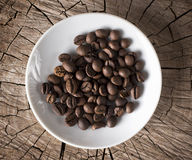 Boisson chaude parfumée de grains de café sur une soucoupe blanche sur la texture en bois Photos stock