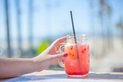 Boisson colorée dans un pot un jour ensoleillé par la plage Photos stock
