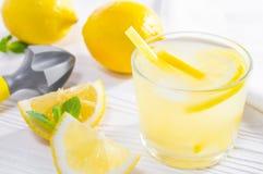 Boisson d'été de citron, ou de limonade, avec les feuilles en bon état et le presse-fruits de main sur la table en bois blanche image libre de droits