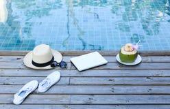 Boisson d'ordinateur portable et de noix de coco par awimming la piscine Photographie stock