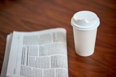 Boisson de café en tasse de papier et journal sur la table Photographie stock