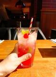 Boisson de coctail d'alcool avec la paille de cerise, de chaux et de lucette sur la table dans le restaurant photo libre de droits