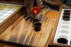 Boisson de liqueur de cerise de Ginja/Ginjinha étant versée dans des tasses de chocolat sur le fond en bois Boisson traditionnell photo libre de droits
