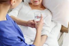 Boisson de participation de médecin au retraité dans l'hôpital Photographie stock libre de droits