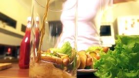 Boisson de versement de kola de femme dans le plat proche en verre avec des hot dogs banque de vidéos