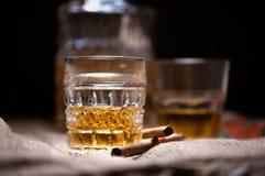 Boisson de whiskey sur les roches avec la bouteille sur le noir Photographie stock libre de droits
