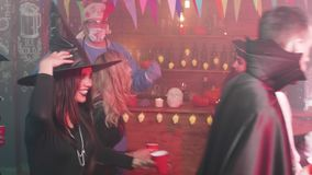 Boisson et danse des jeunes à une partie de Halloween dans un bar local banque de vidéos