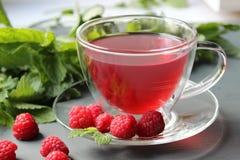Boisson parfumée de thé avec des baies de framboise photographie stock libre de droits