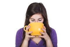 Boisson potable de femme de brune d'une grande tasse jaune d'isolement sur le blanc Image stock