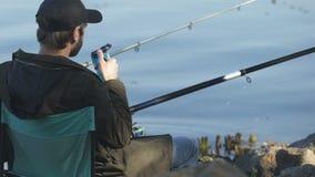 Boisson potable de type de tasse thermo, tenant la canne à pêche, activité de pêche à la ligne banque de vidéos