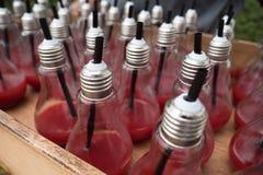Boisson rouge de portion de serveur dans la cuvette avec la forme d'ampoule photos stock